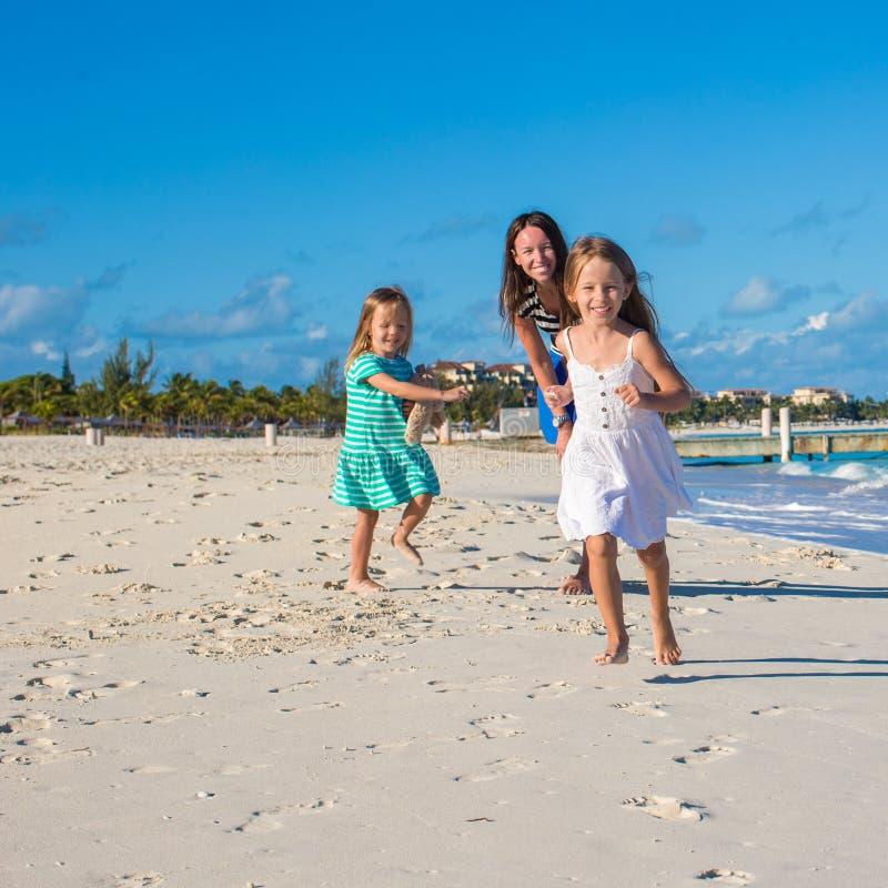 Jonge gelukkige moeder en haar aanbiddelijke dochters die pret hebben bij exotisch strand op zonnige dag stock afbeelding