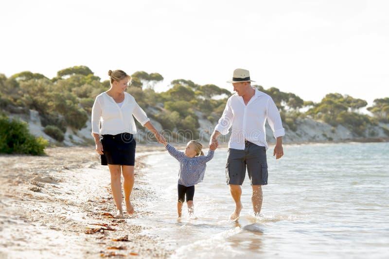 Jonge gelukkige moeder en vader die met weinig dochter op strand in het concept van de familievakantie lopen royalty-vrije stock foto's