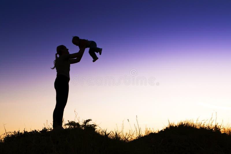 Jonge gelukkige moeder van kinderen in in openlucht. royalty-vrije stock afbeeldingen