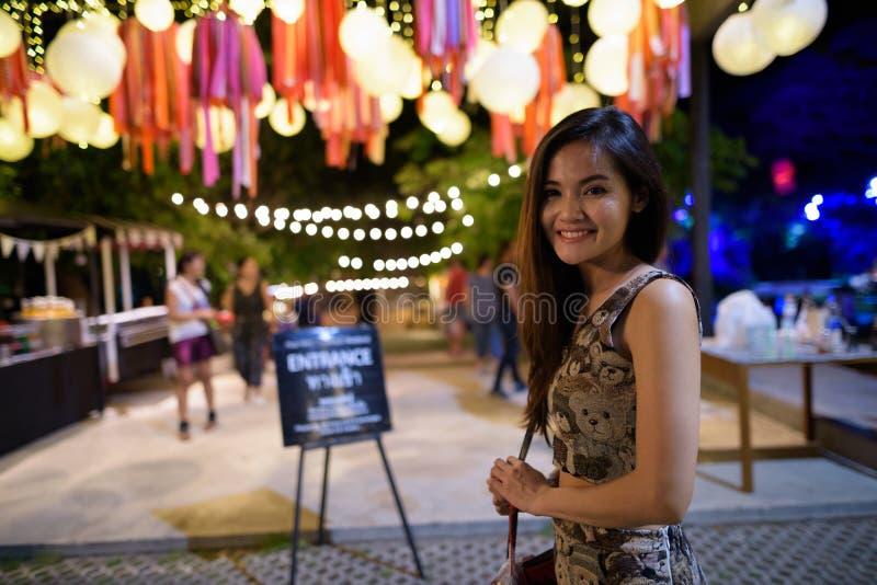 Jonge gelukkige mooie Aziatische vrouw die bij de ingang van ope glimlachen stock foto's