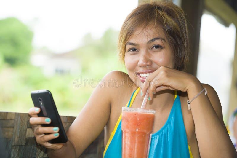 Jonge gelukkige mooie Aziatische vrouw in koffiewinkel die Internet app die op mobiele telefoon gebruiken gezond vruchtensap met  royalty-vrije stock afbeeldingen