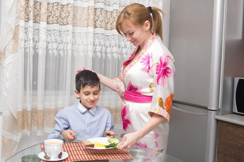 Jonge gelukkige mooie moeder en haar kind het eten stock afbeelding