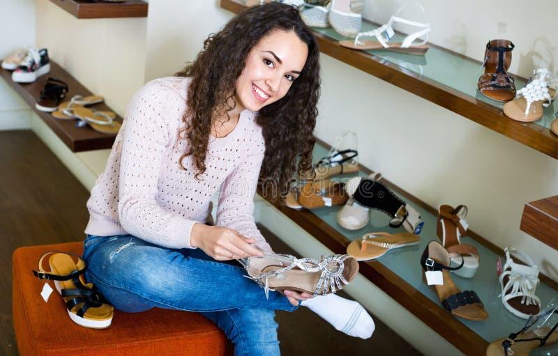 Jonge gelukkige mooie vrouw die bij opslag winkelen royalty-vrije stock afbeeldingen