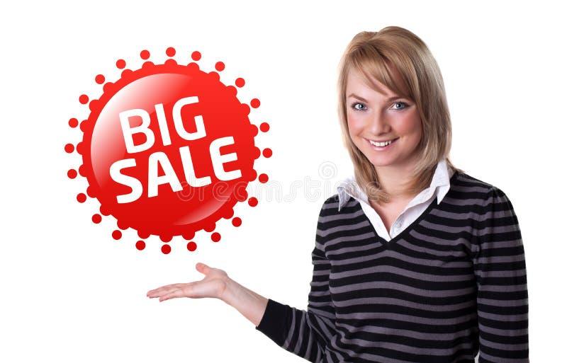 Jonge gelukkige onderneemster die groot verkoopteken voorstelt royalty-vrije stock afbeelding