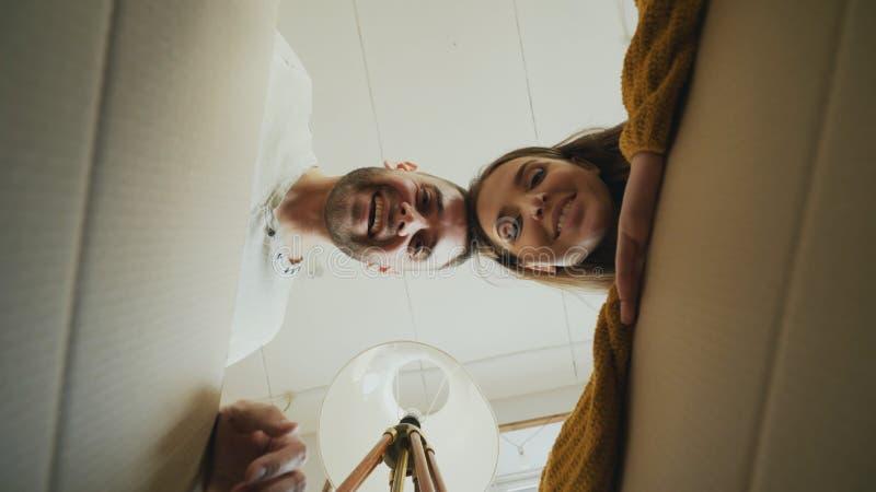 Jonge gelukkige paar het openen kartondoos en het kijken binnen en het sluiten van het die na verhuizing in nieuw huis controlere royalty-vrije stock afbeeldingen