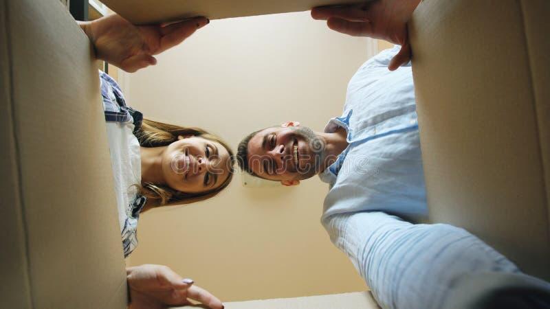 Jonge gelukkige paar het openen kartondoos na verhuizing en het kijken binnen in nieuw huis stock afbeeldingen