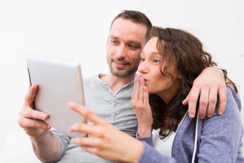 Jonge gelukkige paar video het uitnodigen tablet stock foto's
