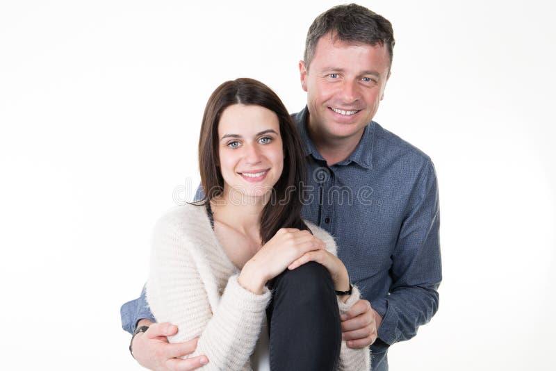jonge gelukkige paarliefde die omhelzend man en vrouwenglimlach glimlachen die op witte achtergrond wordt geïsoleerd royalty-vrije stock fotografie
