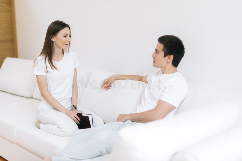 Jonge gelukkige paarzitting op witte bank, die bij elkaar glimlachen royalty-vrije stock afbeelding