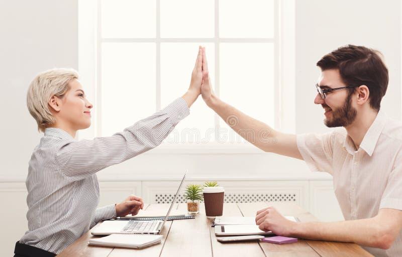 Jonge gelukkige partners in bureau met computer royalty-vrije stock fotografie