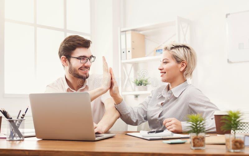 Jonge gelukkige partners in bureau met computer stock foto