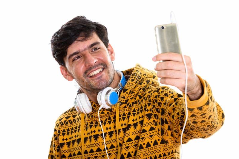 Jonge gelukkige Perzische mens die terwijl rond het dragen van hoofdtelefoons glimlachen stock foto