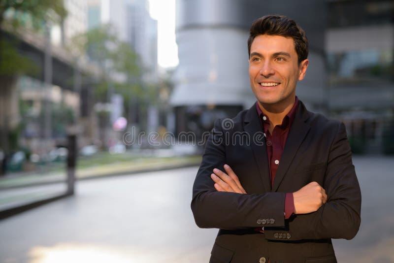 Jonge gelukkige Spaanse zakenman die die met wapens denken buiten het bureaugebouw worden gekruist royalty-vrije stock fotografie