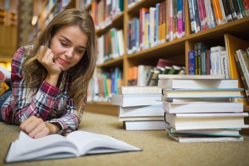 Jonge gelukkige student die op de lezingsboek van de bibliotheekvloer liggen royalty-vrije stock foto