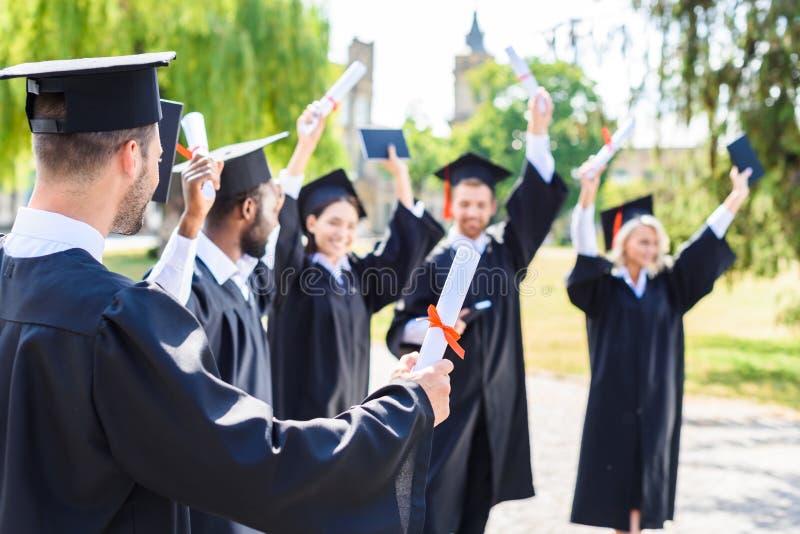 jonge gelukkige studenten die graduatie samen vieren royalty-vrije stock foto's