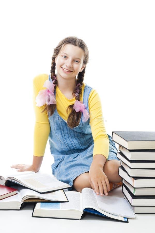 Jonge gelukkige teenagergirl met boeken zit en glimlacht stock afbeeldingen