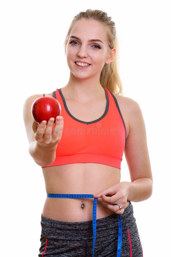 Jonge gelukkige tiener die terwijl het geven van rode appel en meas glimlachen stock foto