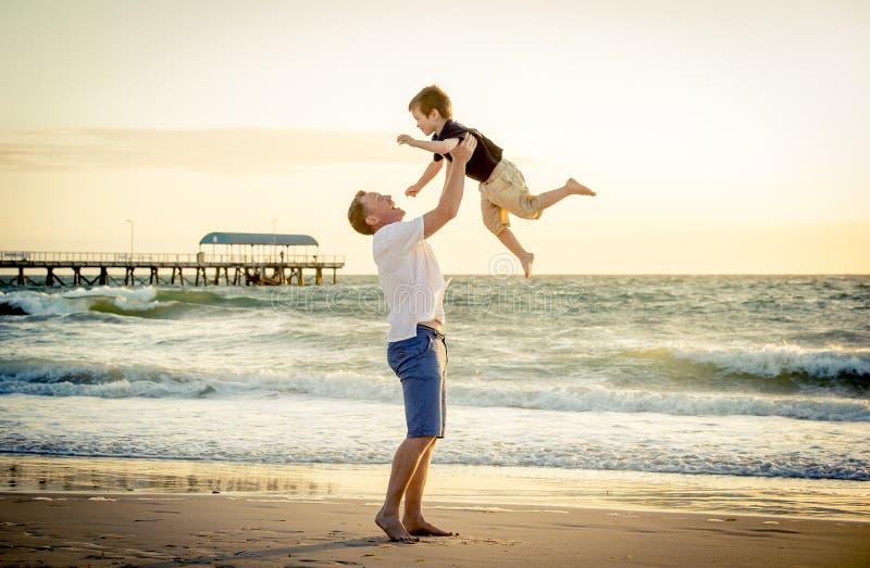 Jonge gelukkige vader die in zijn wapens weinig zoon steunen die hem opzetten bij het strand stock afbeelding