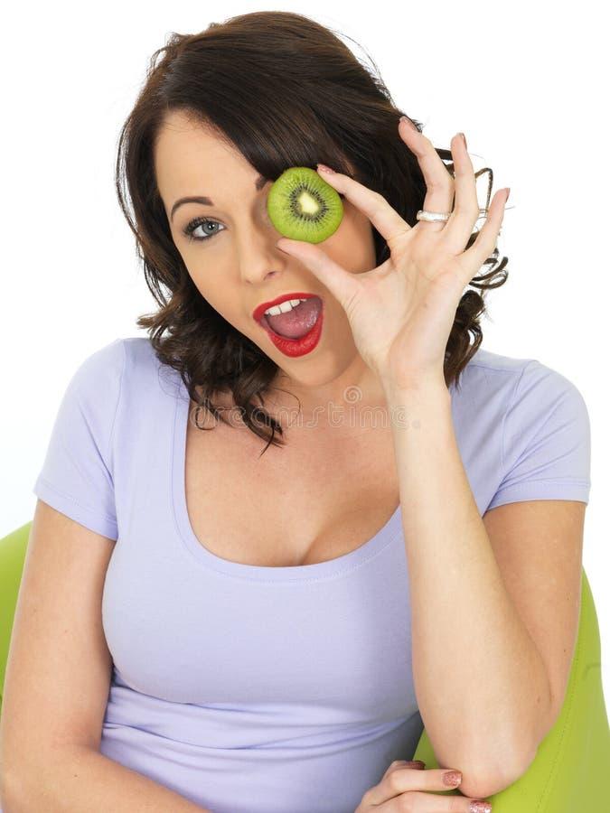 Jonge Gelukkige Verraste Vrouwenholding Vers Rijp Kiwi Fruit stock fotografie