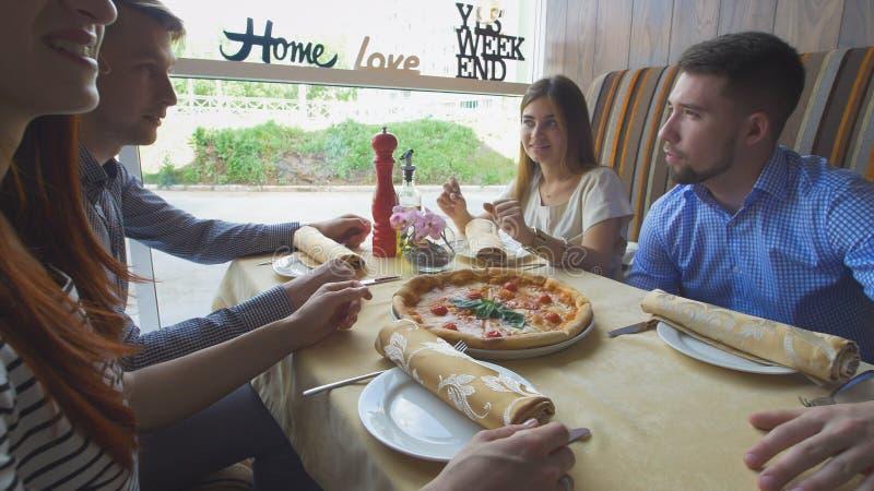 Jonge gelukkige vrienden die van een diner genieten en uit in restaurant hangen royalty-vrije stock foto's