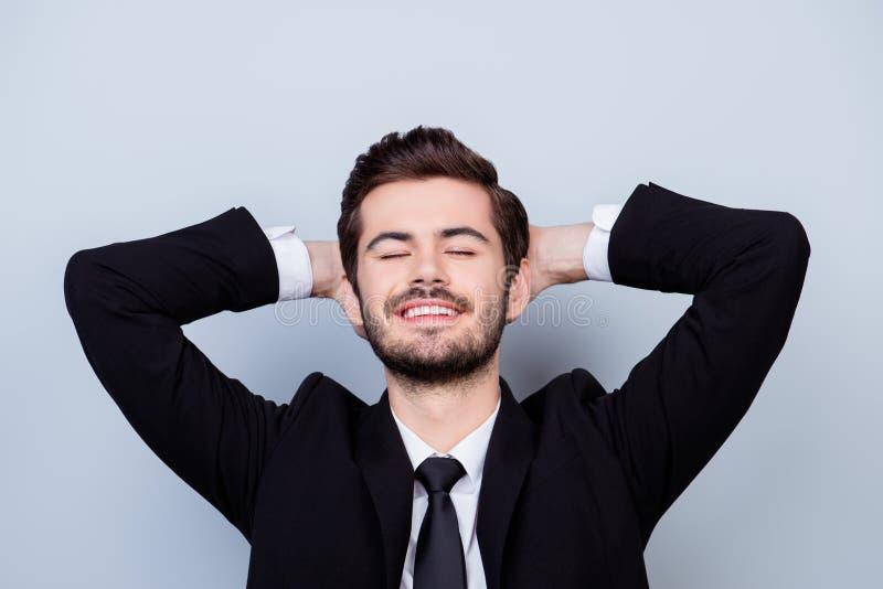 Jonge gelukkige vrolijke glimlachende mens in zwart kostuum die een rust hebben achterin stock foto