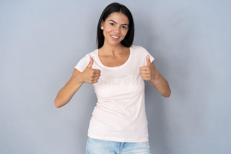 Jonge gelukkige vrolijke vrouw die duim tonen stock foto