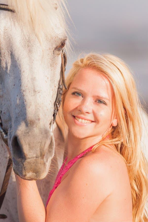 Jonge gelukkige vrouw dichtbij het paard royalty-vrije stock afbeeldingen
