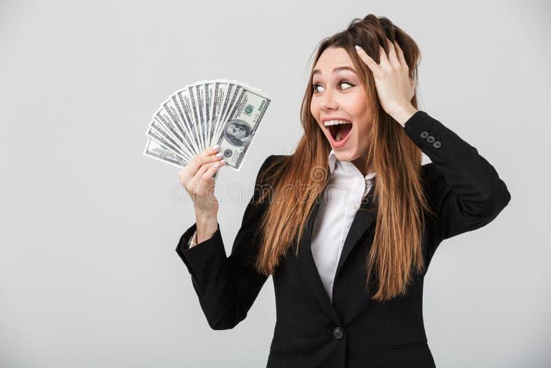 Jonge gelukkige vrouw die dollars in haar geïsoleerde hand en glimlachen bekijken royalty-vrije stock foto's