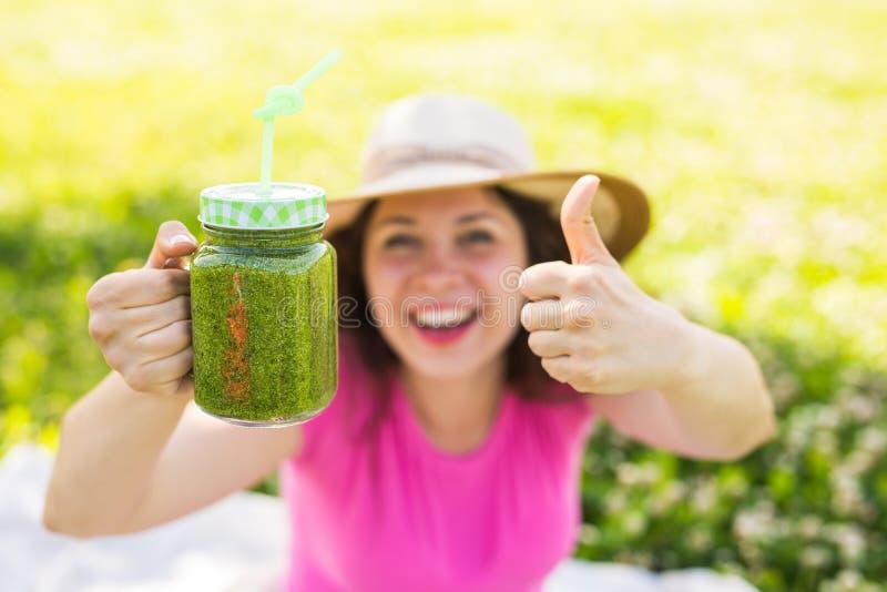 Jonge gelukkige vrouw die duimen met groene smoothies tonen bij een picknick Gezond voedsel, detox en dieetconcept royalty-vrije stock foto