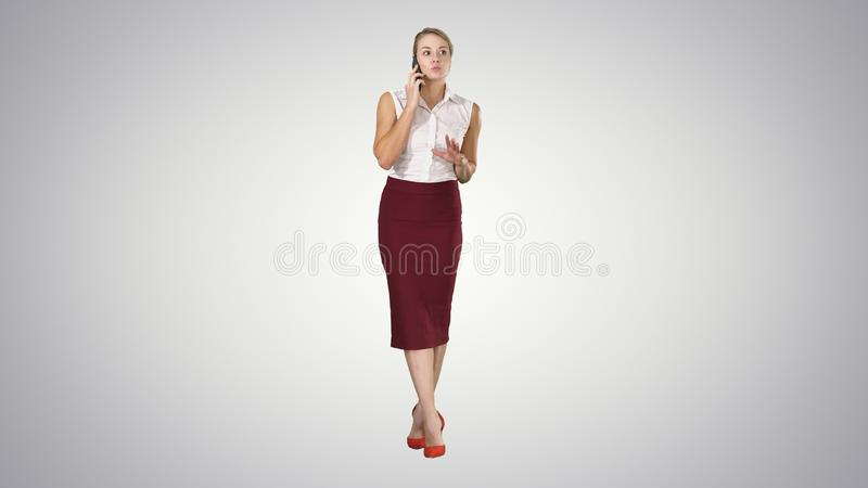 Jonge gelukkige vrouw die en zich op de telefoon op gradiëntachtergrond bevinden spreken stock foto