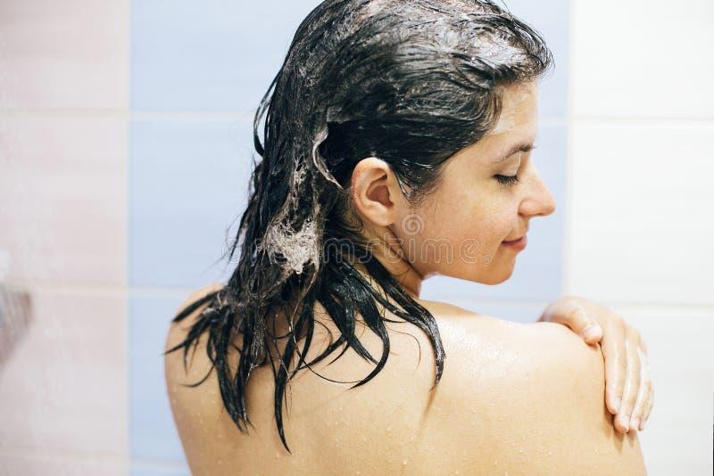 Jonge gelukkige vrouw die haar haar met shampoo, nat haar met schuim wassen Steun van mooi donkerbruin meisje die douche en het g royalty-vrije stock foto's