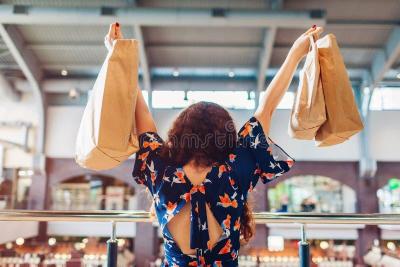 Jonge gelukkige vrouw die handen met het winkelen document zakken in winkelcentrum opheffen stock fotografie