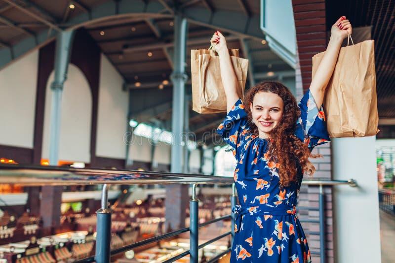 Jonge gelukkige vrouw die handen met het winkelen document zakken in winkelcentrum opheffen stock foto