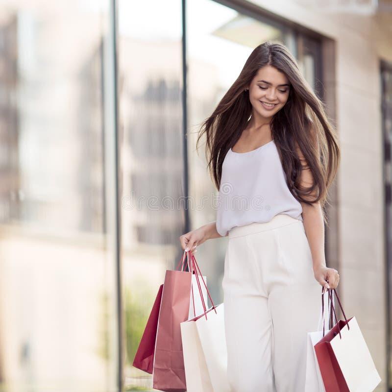 Jonge gelukkige vrouw die met het winkelen zakken op straat lopen stock foto