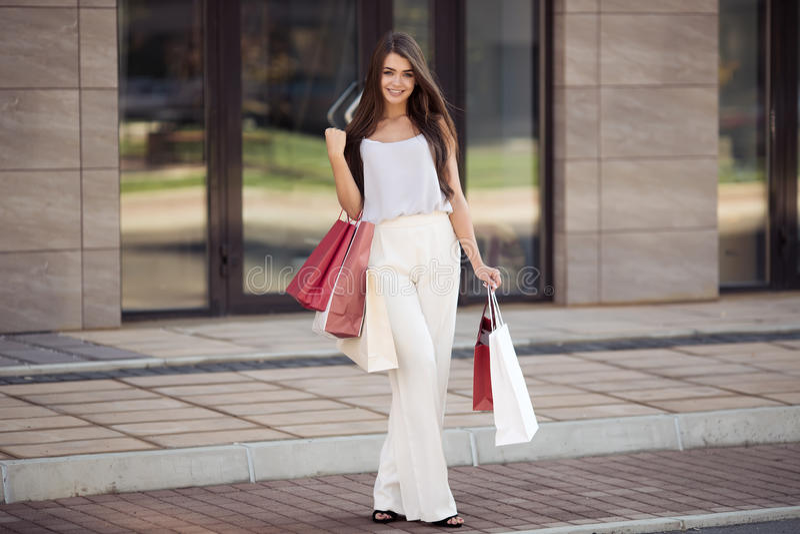 Jonge gelukkige vrouw die met het winkelen zakken op straat lopen stock foto's