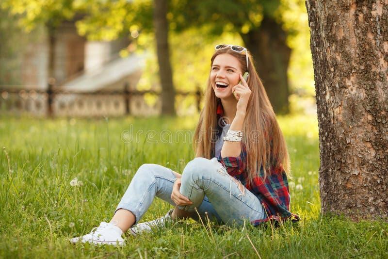 Jonge gelukkige vrouw die op de zitting van de celtelefoon op gras in het park van de de zomerstad spreken Mooi modern meisje in  royalty-vrije stock afbeelding
