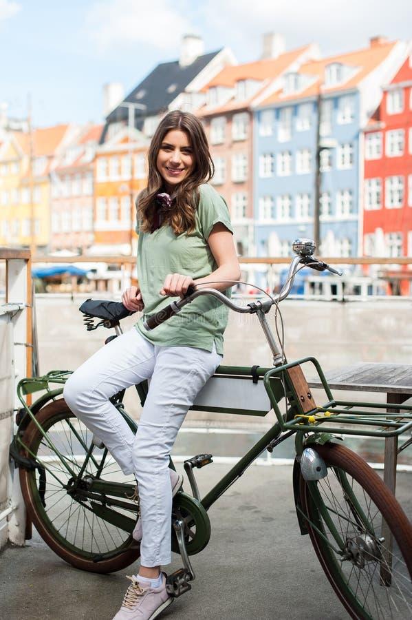 Jonge gelukkige vrouw die op fiets bij camera glimlachen stock afbeelding