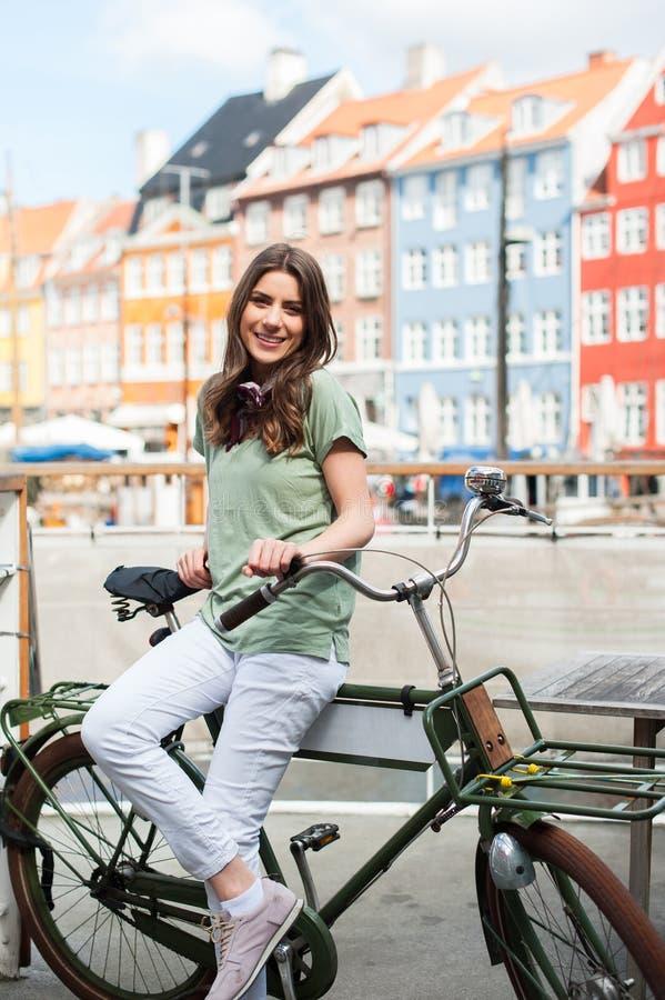 Jonge gelukkige vrouw die op fiets bij camera glimlachen stock foto