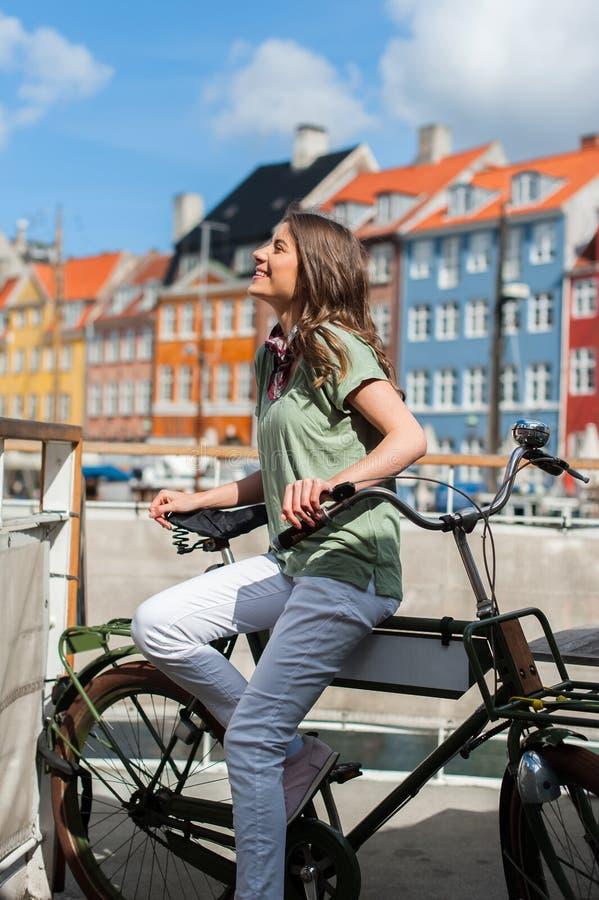 Jonge gelukkige vrouw die op fiets kant kijken royalty-vrije stock fotografie