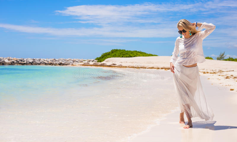 Jonge gelukkige vrouw die op het strand lopen stock fotografie