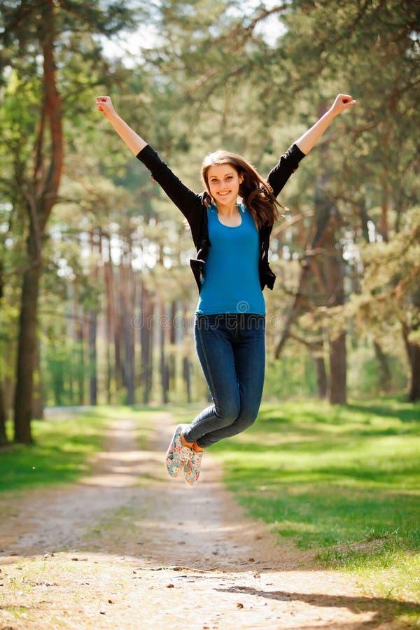 Jonge gelukkige Vrouw die in park in zonnige dag lopen stock foto's