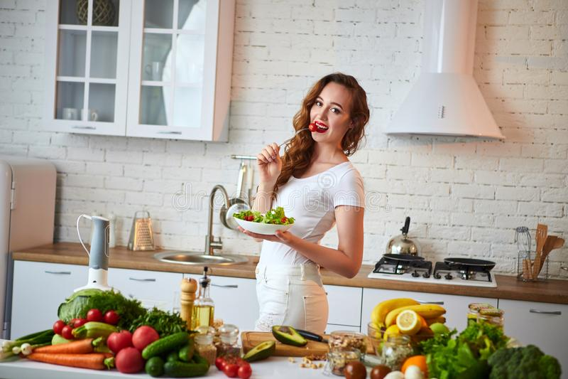 Jonge gelukkige vrouw die salade in de mooie keuken met groene verse ingrediënten binnen eten Gezond voedselconcept stock foto's