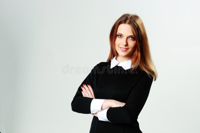 Jonge gelukkige vrouw die zich met gevouwen wapens bevinden royalty-vrije stock afbeelding