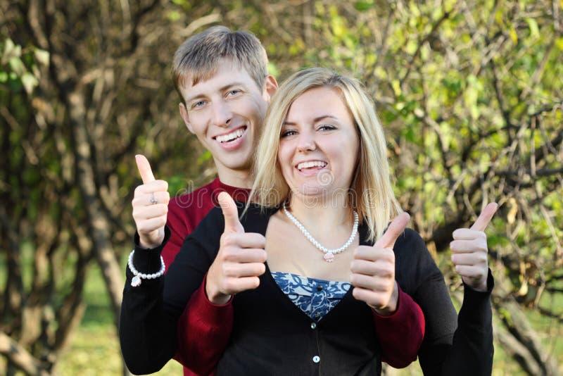 Jonge gelukkige vrouw en man achter haar duimen omhoog in park stock afbeelding