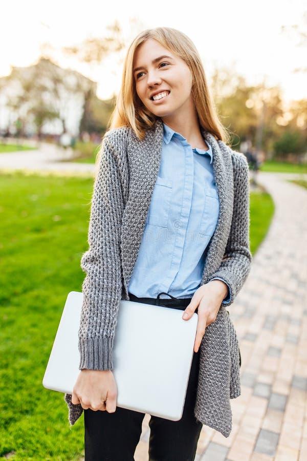 Jonge gelukkige vrouw in het park met laptop op zonsondergangachtergrond royalty-vrije stock foto's