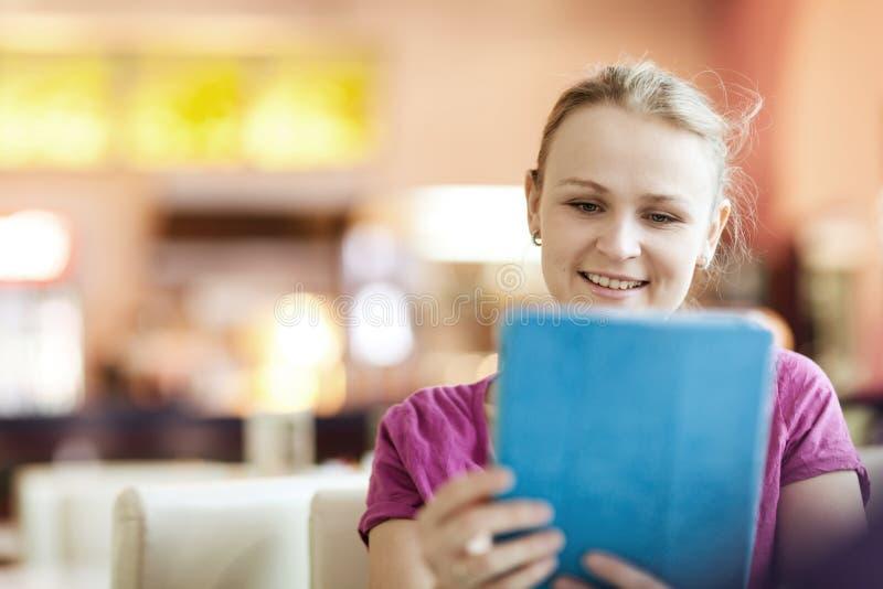 Jonge gelukkige vrouw in koffie met tabletpc royalty-vrije stock afbeeldingen