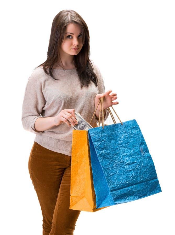 Jonge gelukkige vrouw met het winkelen zakken en het geld van het dollarcontante geld stock foto