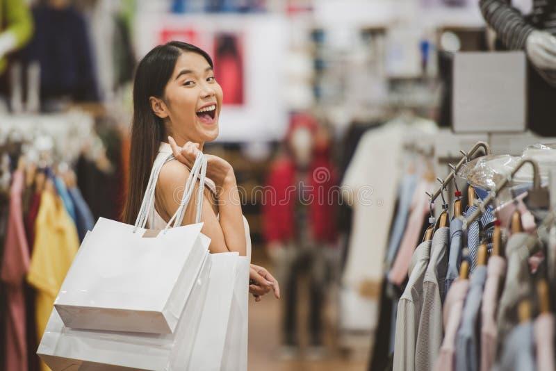 Jonge gelukkige vrouw met het winkelen zakken in stor van de luxekleding royalty-vrije stock fotografie