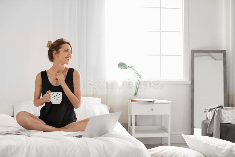Jonge gelukkige vrouw met kop van aromatische koffiezitting op bed thuis royalty-vrije stock foto's