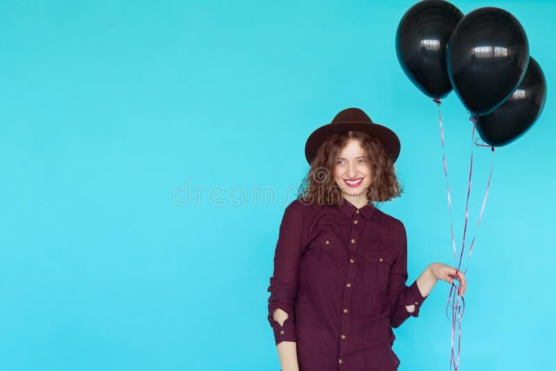Jonge gelukkige vrouw met zwarte ballons die een verjaardag hebben royalty-vrije stock afbeelding